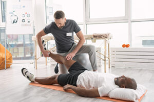 Leg muscles. Smart skillful coach holding patients leg while doing a special rehabilitation exercise