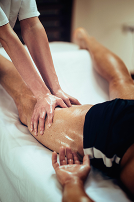 Female physical therapyst massaging leg of male athelete