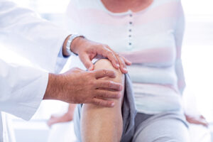 Physiotherapist giving knee therapy to senior woman in clinic